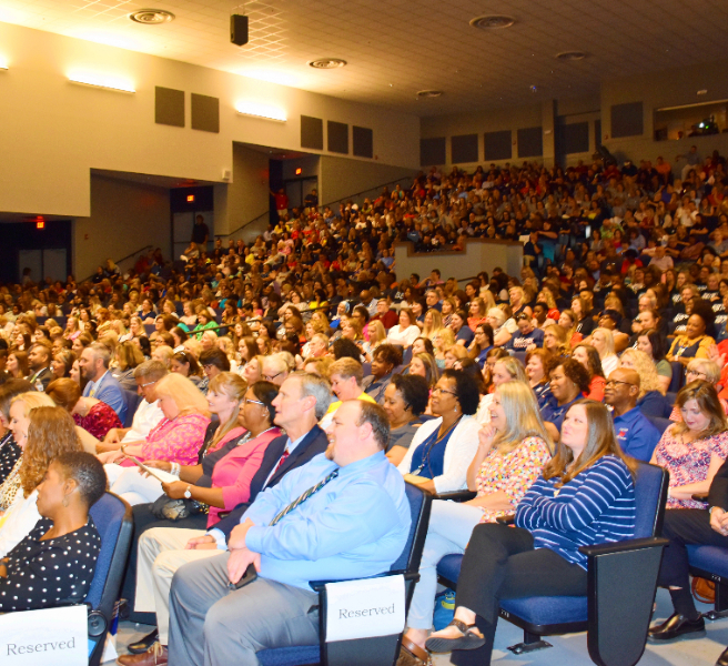 wide angle photo of a packed auditorium of Madison City teachers