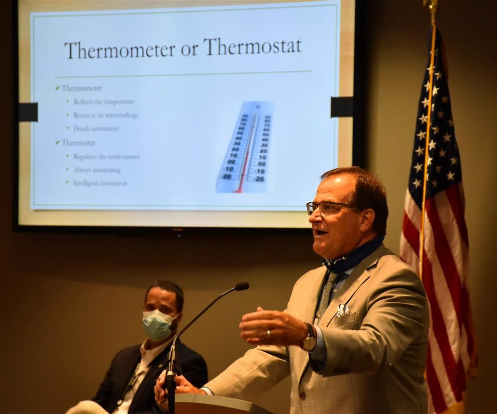 Dr. Nichols at podium in front of a message that asks are you a thermometer or a thermostat