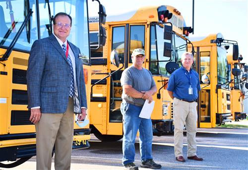 Dr. Nichols in front of schoolbus with shop foreman Shannon Pease and Director  John Wilson