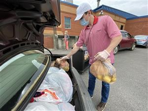 Food prep worker loading food bags in car trunk for family