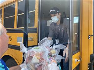 Workers loading a schoolbus with food for delivery