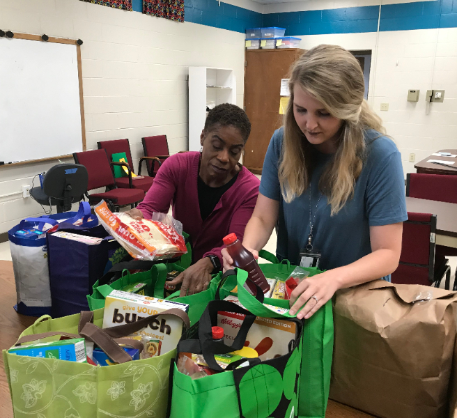 Social worker and principal filling food bags